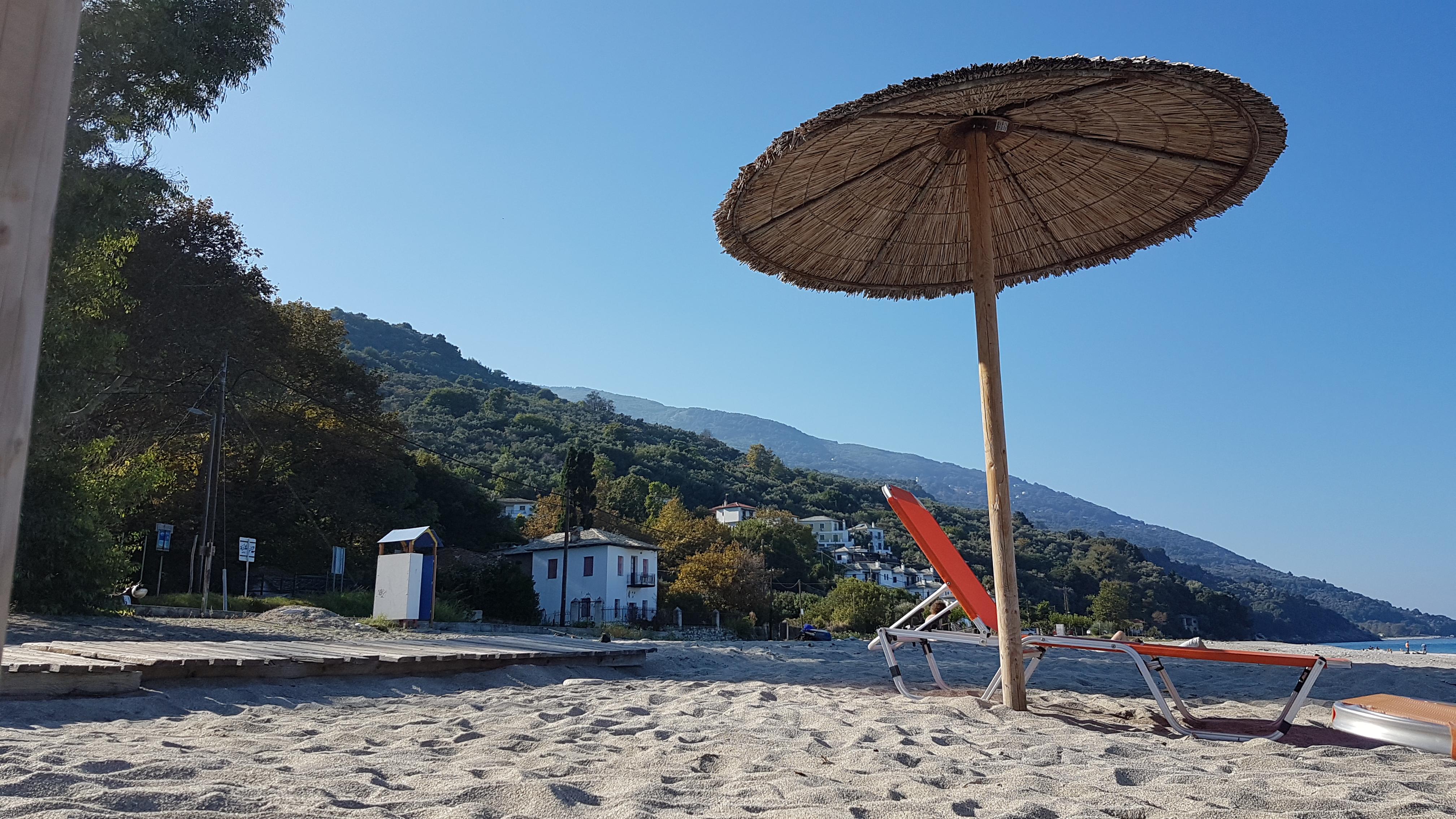 Strand von Chorefto mit einer Strandliege und einem Sonnenschirm aus Schilf