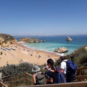 Ein paar Tur de sens Gäste steigen über eine Holztreppe zum Strand hinunter. Dieser besteht aus beeindruckenden Felsen, die wunderschöne Sandasbchnitte umrahmen oder direkt im Wasser stehen