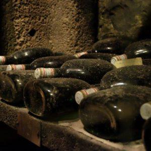 Angestaubte, edle Boxbeutel-Flaschen im Weinkeller von Castell