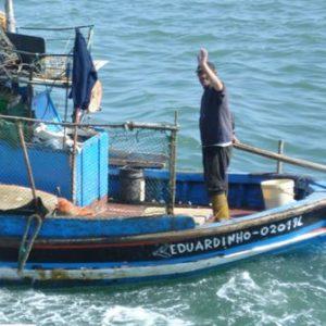 Ein Fischer winkt vom seinem Boot aus dem Betrachter zu.