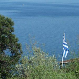 Griechische Flagge vor dem blauen, ägäischen Meer