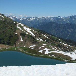 Schneebedecktes Fellhorn mit Bergsee im Vordergrund