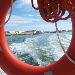 Blick vom Schiff aus durch einen Rettungreifen auf die andalusische Fischerstadt isla Cristina