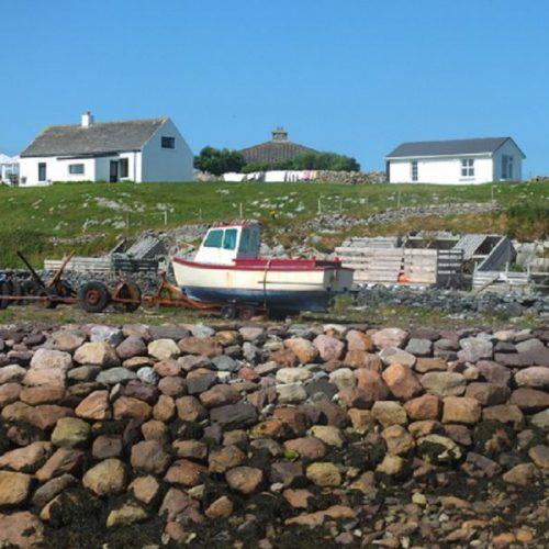 Fischerboot auf Wiese und weiße Häuschen im Hintergrund