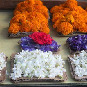 Tagetes- und Jasminblüten werden als Opfergabe vor einem Tempel verkauft