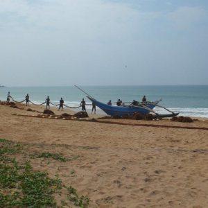 Fischer mit Netzen und Auslegeboot am Strand von Kaluthara