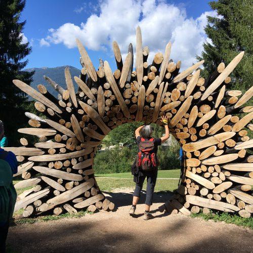 Ein Besucher ertastet ein aus verschiedenen Baumstämen bestehendes Holztor ind der Freiluftausstellung Arte Sella