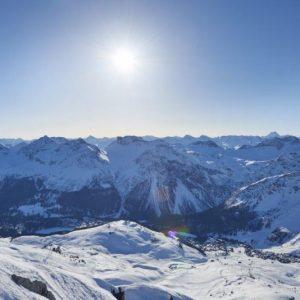 Sonne über der weiß beschneiten Bergkette
