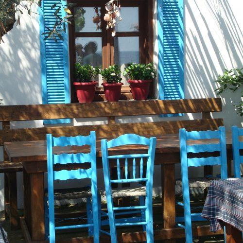 hellblau gestrichene Holzstühle stehen vor einem hellblau gestrichenen Fenster mit Blumenschmuck