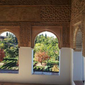 Blick durch verzierte Hufeisenbögen auf den Garten der Alhambra