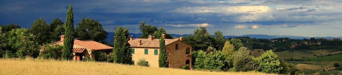 Ein typisch toskanisches Steinhaus hinter einem gelben Weizenfeld