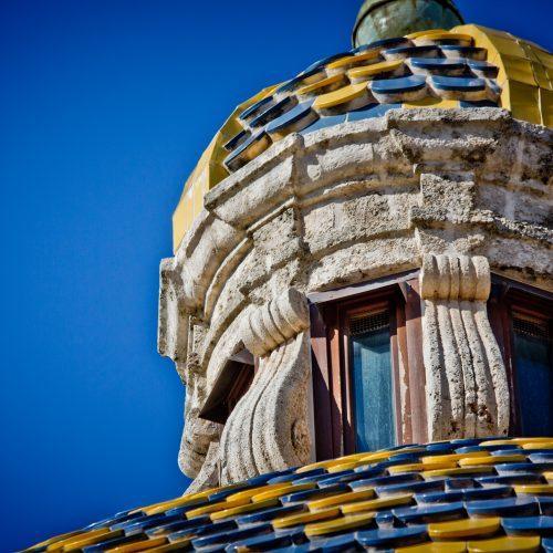 Bunt gekachelte Kirchkuppel vor blauem Himmel in Conversano