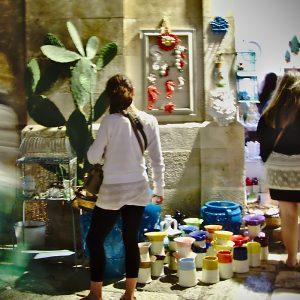 Der Wochenemarkt von Conversano. Käufer und Verkäufer an einem Stand mit bunten Keramikvasen.