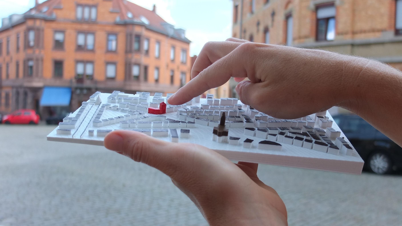 Eine Hand ertastet das Tatsmodel vom Stuttgarter Stadtteil Ostheim. Im Hintergrund sieht man Backstein-Hausfassaden