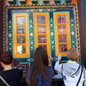 Gruppenteilnehmer ertasten eine bunt bemalte Holztür eines Klosters