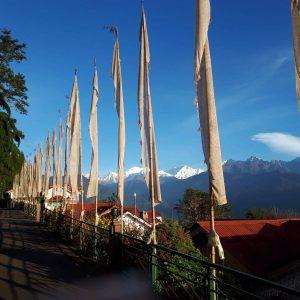 Blick von der Hotelterrassse in Darjeeling auf die schneebedeckten Berge des Himalaya. Im Vordergrund sieht man weiße Fahnen