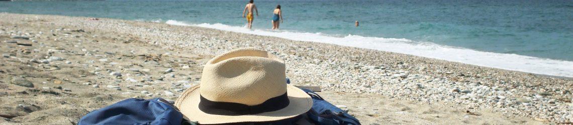 Ein Stroh-Sonnenhut liegt auf einem Wanderrucksack am Strand