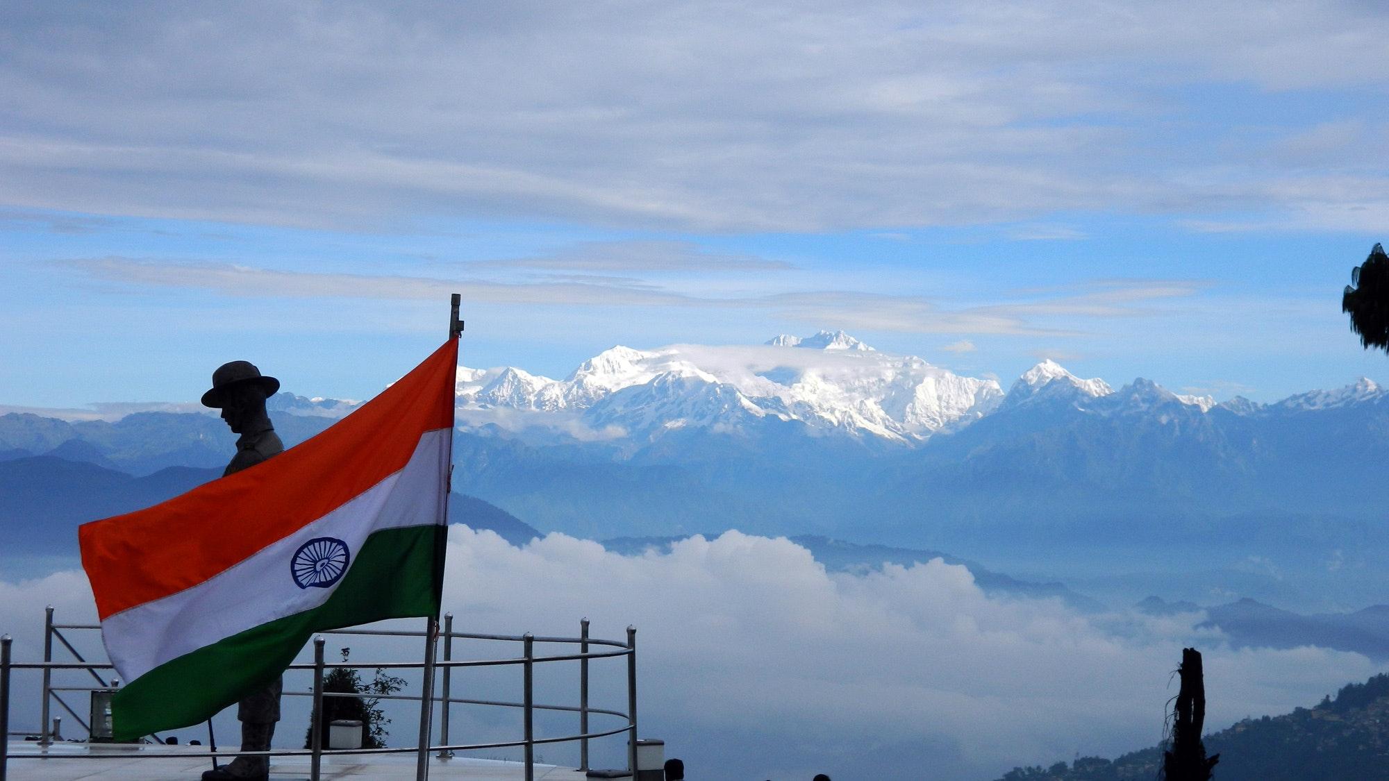 Das vom Schnee bedeckte Bergmassiv des Kangchenjunga. Im Vordergrund weht, neben einer Skulptur auf einem Aussitchtspunkt eine indische Fahne im Wind