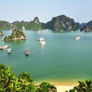 Die Bai Tu Long Bucht mit Kalksteinkegelbergen, Schiffen und einem Sandstrand