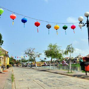Lampions über einer Straße von Hoi An. Die Straße führt direkt entlang eines Flusses
