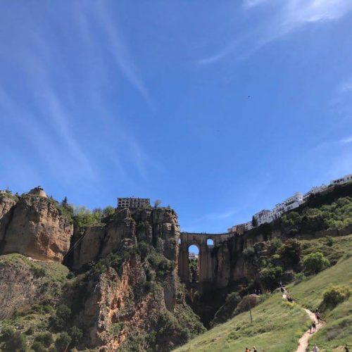 Ronda aus dem Tal gesehen. Beosnders auffällig die hohe Steinbrücke, die die beiden Felsen mit einander verbindet