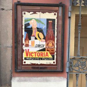 Ein Kachelbild der Biermarke Victoria aus Málaga. Ein Mann sitzt an einem Tisch und trinkt Bier. Er hält einen Strohhut in den Händen und wischt sich mit einem Tuch den Schweiß von der Stirn. Im Hintergrund sieht man das Meer und eine Palme