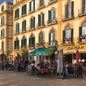 Gelb getünchte Fassaden in der Alstadt von Malaga. Im Vordergrund sieht man die voll besetzte Terrassen der Tapa-Bars