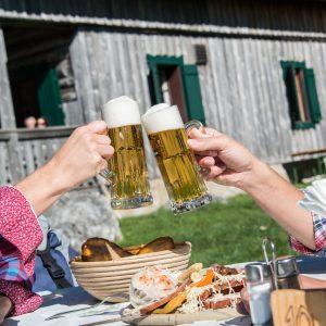 Berghütte. Imvordergrund zwei Händ mit Biergläsern, die sich zuprosten