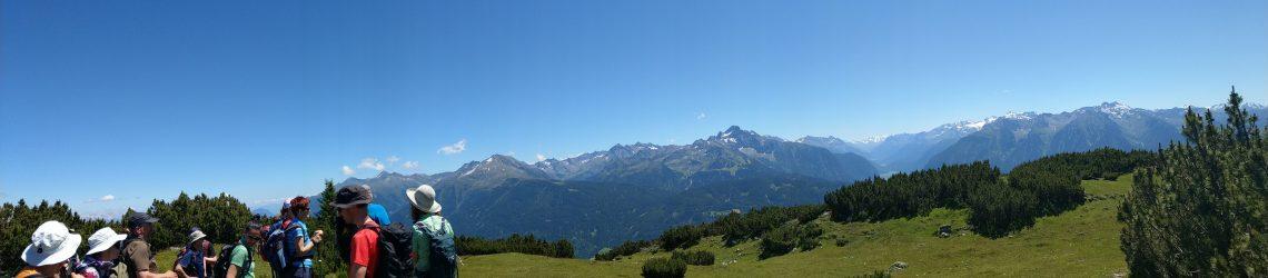 tour de sens Gruppe vor beeindruckender Bergkulisse auf der Alm des Berges Simmering