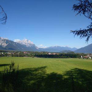 Blick über das saftig grüne Mieminger Plateau, welches von hohen Bergen umgeben ist.