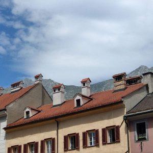 Schornsteine auf den Dächern von Innsbruck vor Bergkulisse