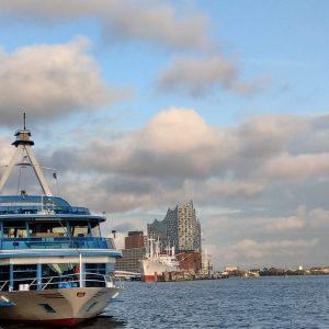 Im Vordergrund sieht man eine Elbfähre auf dem welligen Wasser der Elbe. Im Hintergrund weitere Schiffe und die Elbphilharmonie