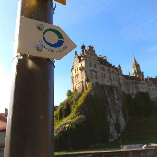 Das Hohenzollernschloss in Sigmaringen. Im Vordergrund das Wanderwegzeichen des Fernwanderwegs