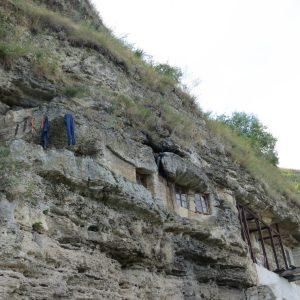 Höhlenkloster Tipowa. Man sieht Fenster im Felsen und zum Trocknen aufgehängte Wäsche