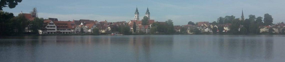 Die Skyline von Bad Waldsee mit dem Stadtsee im Vordergrund.